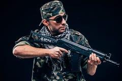 Soldat masqué fortement armé avec le concept noir de fond photo stock
