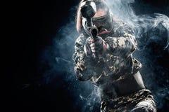 Soldat masqué fortement armé de paintball d'isolement sur le fond noir Concept d'annonce image libre de droits