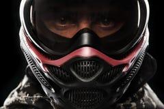 Soldat masqué fortement armé de paintball d'isolement sur le fond noir Concept d'annonce photographie stock