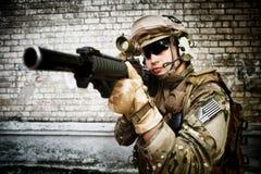 Soldat med ett gevär mot väggen Royaltyfri Bild