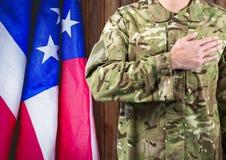 Soldat mit der Hand auf dem Herd und der USA-Flagge hinten Stockfoto