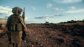 Soldat mit der Waffe, die auf Schießstand auf Hintergrundmilitärfahrzeug steht stock video