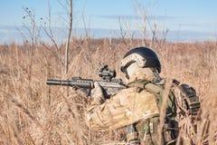 Soldat mit Gewehr im Feldhinterhalt Lizenzfreies Stockbild