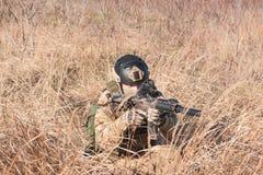Soldat mit Gewehr im Feldhinterhalt Stockfotografie