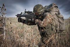 Soldat mit Militärsturzhelm und Gewehr in der Aktion Stockfotografie