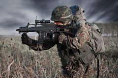 Soldat mit Militärsturzhelm und Gewehr in der Aktion Stockbild