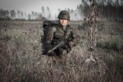 Soldat mit Militärsturzhelm und Gewehr in der Wildnis Stockbilder