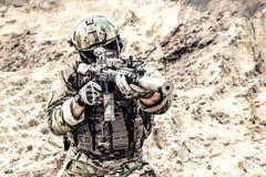 Soldat moderne d'armée visant et tirant dans le désert Photo libre de droits