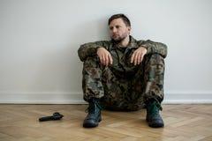 Soldat professionnel fatigué dans l'uniforme vert se reposant sur le plancher à côté d'une arme à feu images libres de droits