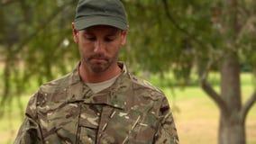 Soldat regardant le PC de comprimé en parc clips vidéos