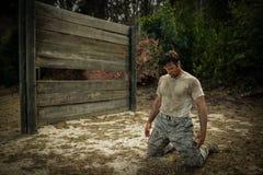 Soldat s'asseyant sur ses genoux photo stock