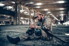 Soldat sitzt aus den Grund und betrachtet sein portables Radio Er hält es mit beiden Händen Kerl hat seins gekurvt Lizenzfreie Stockbilder