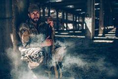 Soldat sitzt hinter Spalte und hält Gewehr nah an seinem Körper Er sitzt sehr auf stille Art Kerl wartet Er Lizenzfreies Stockfoto