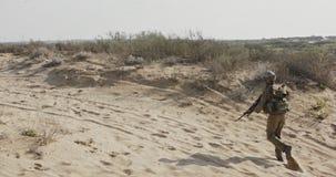 Soldat som kör på en sandkulle under strid, under brand arkivfilmer
