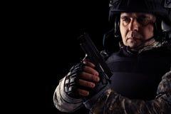 Soldat som siktar med den svarta pistolen bild p? en m?rk bakgrund arkivfoton