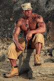 Soldat som sitter i grusgrop Arkivfoto