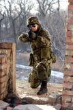 Soldat som sitter nära väggen med en tryckspruta arkivfoton