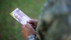 Soldat tenant la photo heureuse de couples, amie absente, souvenirs, séparation banque de vidéos