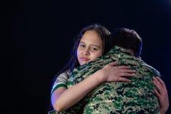 Soldat umarmt Tochter auf der Abreise oder dem Zurückbringen lizenzfreies stockbild