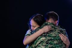 Soldat umarmt Tochter auf der Abreise oder dem Zurückbringen lizenzfreies stockfoto