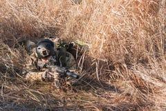 Soldat in voller NATO-Uniform, die in den Büschen sich versteckt Lizenzfreie Stockbilder