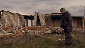 Soldatarbetena med en min avkännare i fördärvar av hus i sökande av miner och sprängmedel stock video