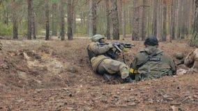 Soldaten in der Tarnung mit Kampfwaffen werden im Schutz des Waldes, das Militärkonzept gefeuert stock video footage