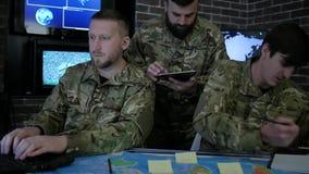 Soldaten in der Uniform, arbeitend in der digitalen Tablette, im Notizbuch und im Laptop, im Militärstützpunkt und besprechen Ang stock footage