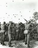 Soldaten, die auf den Feind mit Fallschirm abspringt in Feld schießen Lizenzfreies Stockfoto