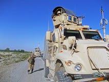 Soldaten, die den Bereich auf einer Straße in Afghanistan suchen Stockbild