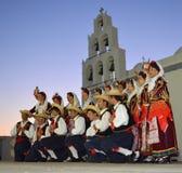 Soldaten för den traditionella dansen i dräkt poserar framme av kyrka för aftonkapacitet arkivbilder