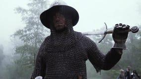 Soldaten i chainmailharnesk med ett svärd på hans skuldra ser omkring arkivfilmer