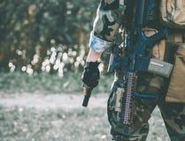 Soldaten i kapaciteten av uppgifter i kamouflage och skyddande handskar som rymmer ett vapen Arkivbilder