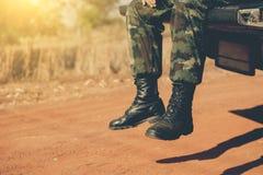 Soldaten lägger benen på ryggen på baksidan av bilen som är borttappad i krigbegrepp Royaltyfri Foto