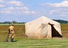 Soldaten står bredvid ett gammalt militärt tält på ängen royaltyfri foto
