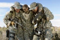 Soldater i bärande kollega för fält Arkivfoton
