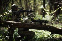 Soldater i kamouflage bland träd fotografering för bildbyråer