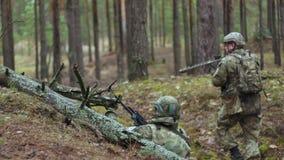 Soldater i kamouflage med stridvapen avfyras i skyddet av skogen, det militära begreppet arkivfilmer