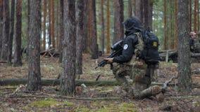 Soldater i kamouflage med stridvapen avfyras i skyddet av skogen, det militära begreppet lager videofilmer