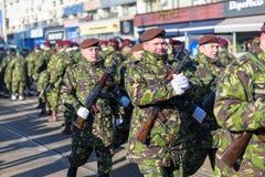 Soldater i militär gör grön enhetlig marsch och att fira arkivfoton