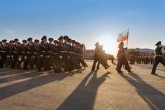 Soldater med flaggamarsch ståtar på Arkivbild