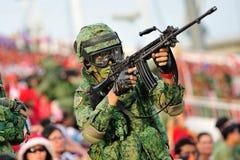 Soldater som flyttar sig bland åskådarna under nationell dag, ståtar repetitionen (NDP) 2013 Arkivfoto