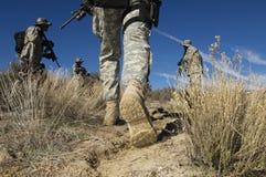 Soldater som går i öken Arkivbild