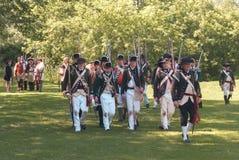 Soldater som marscherar på den svarta liten vikbyn Arkivbild