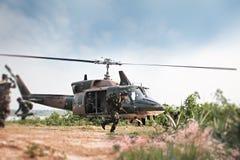 Soldater som rymmer vapnet och hoppar från helikoptern fotografering för bildbyråer