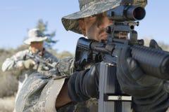 Soldater som siktar gevär i fält arkivbild