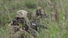 Soldater som sitter i väntan i gräset Militär i armar över kullen stock video
