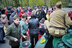 Soldater som ut räcker mat till förbipasserande på dagen av det andra världskriget royaltyfri bild