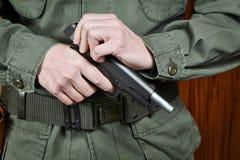 Soldatfensterladen, der Pistolengewehr spannt lizenzfreie stockfotos