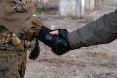 Soldathändedruck auf Krieg stockfoto